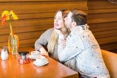 Jeune homme embrassant son amie dans la joue tout en ayant du thé ensemble dans un café Images stock