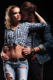 Jeune homme embrassant son amie du dos Photographie stock