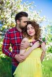 Jeune homme embrassant son amie en parc Photographie stock