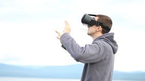 Jeune homme employant des verres de réalité virtuelle et fumant la cigarette outdoors banque de vidéos