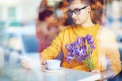 Jeune homme employant la date de attente de Smartphone en café Photos libres de droits
