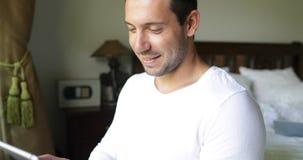 Jeune homme employant le café Guy Chatting Online In Bedroom de sourire de boissons de tablette banque de vidéos