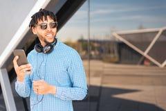 Jeune homme employant le sien téléphone et extérieur heureux d'isolement étroit de écoute de musique photos libres de droits