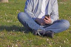 Jeune homme employant le sien téléphone tout en se reposant dehors Image libre de droits