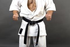Jeune homme en art martial de formation de kimono blanc et de ceinture noire image stock