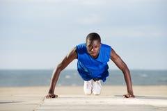 Jeune homme en bonne santé faisant des pousées sur la plage Images stock