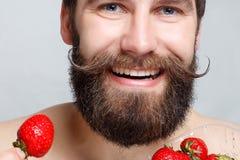 Jeune homme en gros plan de portrait tenant une fraise et un sourire Photographie stock