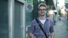 Jeune homme en verres appréciant sa musique tout en marchant dans la rue banque de vidéos