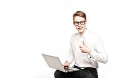 Jeune homme en verres avec l'ordinateur portable avec des pouces d'émotion  image libre de droits