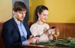 Jeune homme engagé s'asseyant avec son amie au restaurant Photo libre de droits