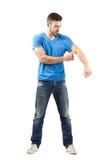 Jeune homme enlevant sa chemise tout en tenant la douille Photographie stock libre de droits