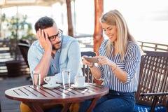 Jeune homme ennuyé attendant son amie pour cesser d'utiliser le téléphone images libres de droits
