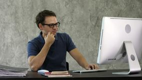 Jeune homme ennuyé au bureau devant l'ordinateur photographie stock