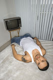 Jeune homme ennuyé se trouvant sur le bâti Photographie stock libre de droits