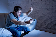 Jeune homme enthousiaste à la maison s'asseyant sur le sofa de salon jouant des jeux vidéo utilisant la manette à télécommande Photographie stock libre de droits