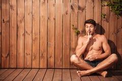 Jeune homme enthousiaste beau reposant et montrant le geste de silence Photo stock