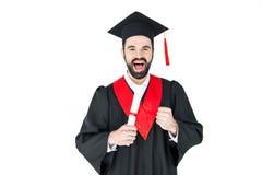 Jeune homme enthousiaste dans le chapeau d'obtention du diplôme tenant le diplôme et triomphant Image stock