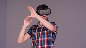 Jeune homme enthousiaste en verres de VR faisant des gestes activement dans le ciel Photos stock