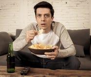 Jeune homme enthousiaste et heureux s'asseyant sur le divan regardant la TV Concept de programmation de TV images stock
