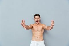 Jeune homme enthousiaste heureux avec les mains ouvertes prêtes pour étreindre Image libre de droits