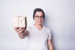 Jeune homme enthousiaste jugeant le présent d'isolement sur le fond blanc photographie stock