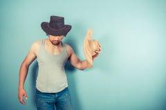Jeune homme essayant sur des chapeaux Photo stock