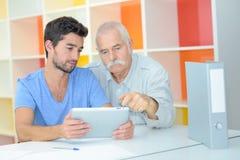 Jeune homme et aîné à l'aide du comprimé numérique Photos libres de droits