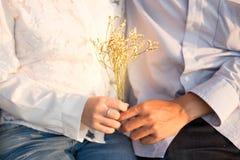 Jeune homme et amie tenant la fleur blanche de bouquet dans leur h Image stock