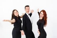 Jeune homme et deux femmes dans le noir sur un fond blanc Images stock