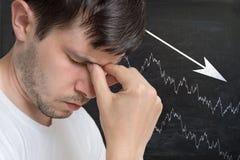 Jeune homme et diagramme malheureux et déçus avec la flèche vers le bas sur le tableau noir à l'arrière-plan Photographie stock libre de droits