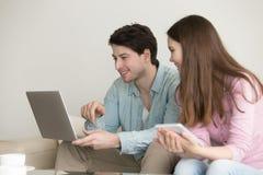 Jeune homme et femme à l'aide de l'ordinateur portable, comprimé, parlant, onli de achat photos stock