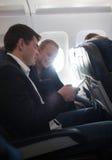 Jeune homme et femme à l'aide du téléphone portable dans l'avion Photo libre de droits