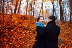 Jeune homme et femme étreignant en parc, feuilles de rouge sur des arbres, octobre Image stock