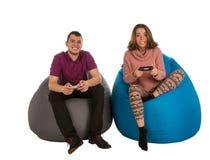 Jeune homme et femme attirants s'asseyant sur le sac à haricots bleu et gris photo libre de droits