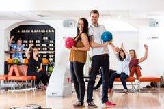 Jeune homme et femme avec des boules de bowling dans le club Photo stock