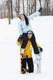 Jeune homme et femme avec des surfs des neiges de treir Photo libre de droits