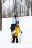 Jeune homme et femme avec des surfs des neiges de treir Images libres de droits