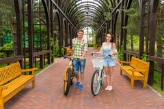 Jeune homme et femme avec des vélos dans l'arcade Image libre de droits