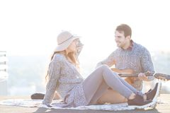 Jeune homme et femme avec la guitare ayant l'amusement dehors Photos stock