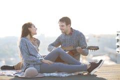 Jeune homme et femme avec la guitare ayant l'amusement dehors Photos libres de droits