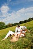 Jeune homme et femme ayant le pique-nique dans le pré Photos libres de droits