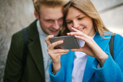Jeune homme et femme blonds regardant sur le smartphone et le sourire Images libres de droits