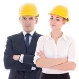 Jeune homme et femme casques de s dans constructeur 'd'isolement sur le blanc Photos stock