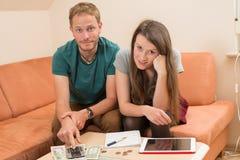 Jeune homme et femme comptant son argent Photos stock