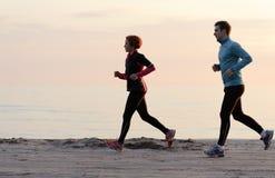 Jeune homme et femme courant le long du bord de mer Photos stock