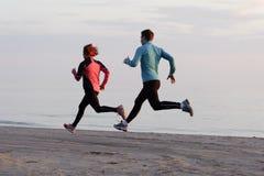 Jeune homme et femme courant le long du bord de mer Photographie stock