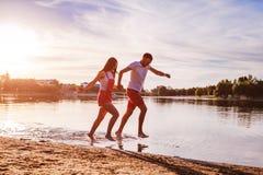 Jeune homme et femme courant sur la berge d'été Couples ayant l'amusement au coucher du soleil Refroidissement de types Photo libre de droits