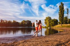 Jeune homme et femme courant sur la berge d'été Couples ayant l'amusement au coucher du soleil Refroidissement de types Images stock