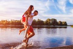 Jeune homme et femme courant sur la berge d'été Couples ayant l'amusement au coucher du soleil Refroidissement de types Photographie stock libre de droits