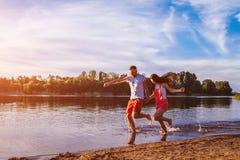 Jeune homme et femme courant sur la berge d'été Couples heureux ayant l'amusement au coucher du soleil Refroidissement de types Photo libre de droits